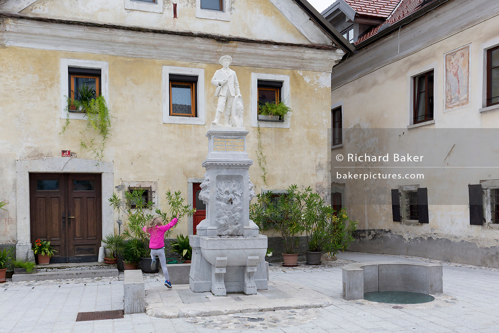 A child plays in front of the fountain dedicated to the Slovenian entrepreneur and patron Josipina Hocevar, in the rural Slovenian town of Radovljica, on 22nd June 2018, in Radovljica, Slovenia.
