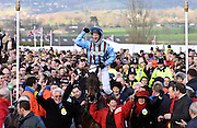 """Gold Cup winning jockey Jim Culloty riding race horse """"Best Mate"""" makes his way triumphantly through the crowds at the Cheltenham National Hunt Festival."""