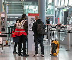"© Licensed to London News Pictures. 24/11/2020. London, UK. Staff talk to a passenger at a Covid testing centre at London Heathrow Terminal 5 today. Minister for Transport Grant Shapps has announced that quarantine for air travellers will drop to 5 days from mid December if they take a private Covid test. Under the new ""test to release"" scheme passengers who test negative after 5 days self-isolation will be able to carry on with their normal lives. Photo credit: Alex Lentati/LNP"