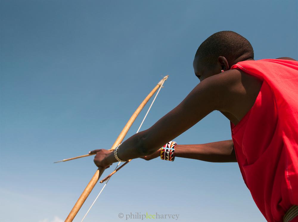 Maasai tribesman with bow and arrow, Maasai Mara, Kenya.