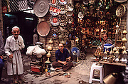 A coppersmith sits and works on an ancient craft passed down through generations in the narrow alleyways of Souk Al Safafeer. <br /> <br /> Baghdad, Iraq <br /> September 2001