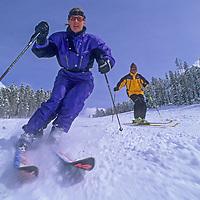 Skiers cruise down a groomed run at Montana's Big Sky resort.