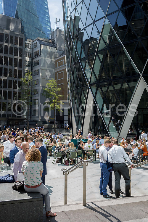 Lunchtime City workers enjoy drinks in summer sunshine beneath the Swiss Re building aka The Gherkin, in the City of London, the capitals financial district aka the Square Mile, on 22nd August 2019, in London, England.