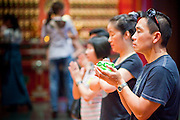 Apr. 28 -- SINGAPORE:  People pray and make merit in the Buddha Tooth Relic Temple in the Chinatown neighborhood of Singapore. The temple has a tooth from the Buddha. The temple, which opened in 2007, has become one of the most important Buddhist temples in Singapore.     PHOTO BY JACK KURTZ
