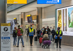 © Licensed to London News Pictures. 16/02/2021. London, UK. Officials escort passengers through Terminal 5 as members of the public walk past at London Heathrow this morning as quarantine hotels near Heathrow start to fill up with travellers from red list countries. From yesterday, (Monday 15 February 2021) anyone arriving from a red-list destination must quarantine at a designated hotel and pay a hotel fee of £1,750 for a 10 day quarantine period. Photo credit: Alex Lentati/LNP
