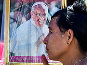 30 NOVEMBER 2017 - YANGON, MYANMAR:   A woman on the street uses a portrait of the Pope as a sun shield during the Papal Mass at St. Mary's Cathedral in Yangon. Thursday's mass was his last public appearance in Myanmar. From Myanmar the Pope went on to neighboring Bangladesh.    PHOTO BY JACK KURTZ