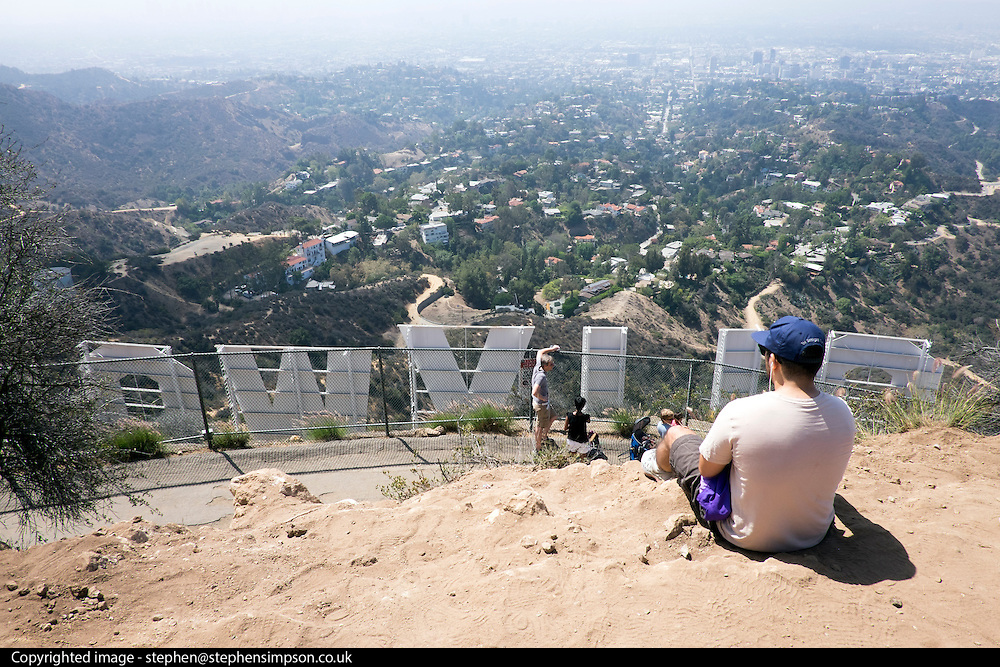 © Licensed to London News Pictures. 09/08/2015. Los Angeles, USA. Tourists take in a view of the Hollywood sign from behind in Los Angeles. Photo credit : Stephen Simpson/LNP