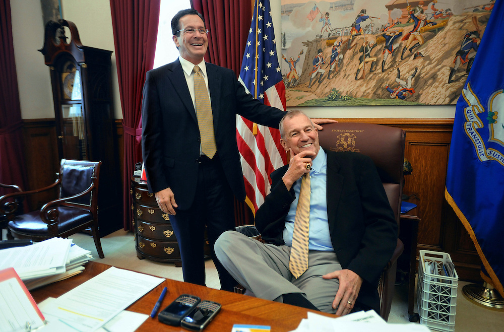 Connecticut men's basketball coach Jim Calhoun, right, sits in the chair of Connecticut Gov. Dannel P. Malloy, left, during a visit to Malloy's office for Husky Day at the Capitol in Hartford, Conn., Wednesday, April 27, 2011. (AP Photo/Jessica Hill)