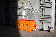 Concrete and plastic moulded patterns in London, United Kingdom. Colourful road block barriers interact with a particularly patterned architectural detail.