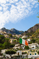 Positano, Italy, September 16 2017. An italian flag flies in the breeze beneath the mountainside buildings of Positano, Italy. © Paul Davey