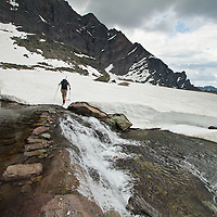 A backpacker crosses a river of snow-melt near Sperry Chalet in Glacier National Park during an early summer backpacking trip.