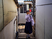 """20 JUNE 2017 - BANGKOK, THAILAND: A schoolgirl walks home in a community along the Chao Phraya River south of Krung Thon Bridge. This is one of the first parts of the riverbank that is scheduled to be redeveloped. The communities along the river don't know what's going to happen when the redevelopment starts. The Chao Phraya promenade is development project of parks, walkways and recreational areas on the Chao Phraya River between Pin Klao and Phra Nang Klao Bridges. The 14 kilometer long promenade will cost approximately 14 billion Baht (407 million US Dollars). The project involves the forced eviction of more than 200 communities of people who live along the river, a dozen riverfront  temples, several schools, and privately-owned piers on both sides of the Chao Phraya River. Construction is scheduled on the project is scheduled to start in early 2016. There has been very little public input on the planned redevelopment. The Thai government is also cracking down on homes built over the river, such homes are said to be in violation of the """"Navigation in Thai Waters Act."""" Owners face fines and the possibility that their homes will be torn down.              PHOTO BY JACK KURTZ"""