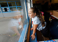 Kindergarten student Daneliz Echevarria checks the weather outside during the first day of school at Gaffney Elementary School in New Britain, Conn.
