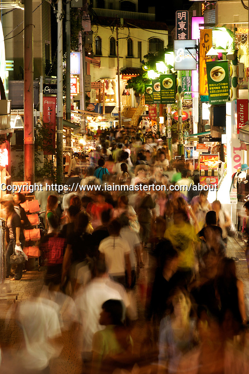 Motion blur image of crowds of people in Takeshita Street at night in trendy Harajuku District of Tokyo Japan