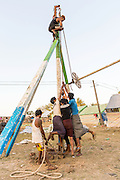 Men pulling rope to raise ferris wheel at fair, Pathein