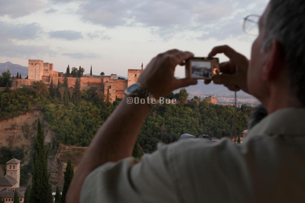 person photographing the Al Alhambra from Plaza San Nicolas, Granada Spain