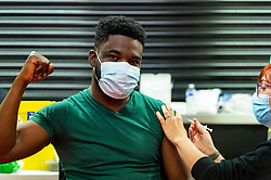 """© Licensed to London News Pictures. 27/06/2021. WATFORD, UK. Kyei Yeboah (aged 30) receives a first dose of the Pfizer vaccine at a pop-up mass vaccination clinic at Watford FC's Vicarage Road Stadium as part of the """"Grab a jab"""" campaign. The NHS is also promoting a number of walk-in clinics this weekend across the capital to try to increase the number of over 18s receiving a jab as cases of the Delta variant are reported to be on the rise..  Photo credit: Stephen Chung/LNP"""