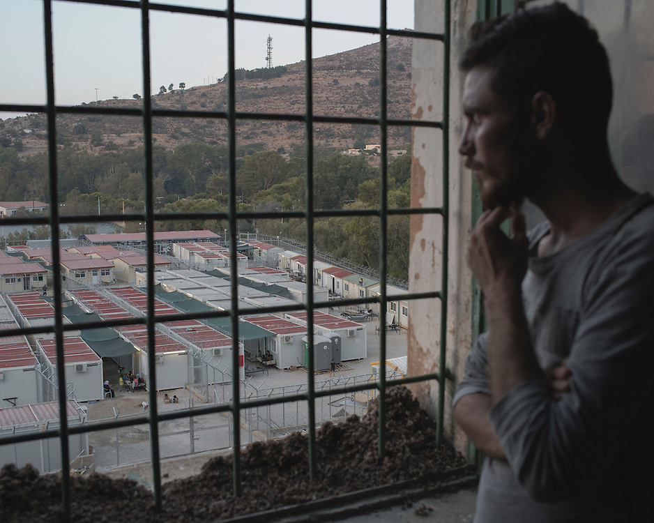Yazidi Hazim Elias Khadeda, 22, looking at the Leros 'Hotspot', an EU-run migrant's reception centre opened in the grounds of the former Lepida psychiatric hospital (from which the view is taken).<br /> <br /> The Hot Spot in Lepida opened on the 26th of February 2016 in the grounds of the former Lepida psychiatric hospital.  At the beginning it served as a registration camp for refugees and migrants who were travelling to Europe through Greece but since the closure of the borders in March 2016 it serves as a permanent camp. People are allowed to go out, they have three meals a day, the prefabricated huts have a bathroom and are air-conditioned and compering to other refugee camps in Greece the conditions are bearable.