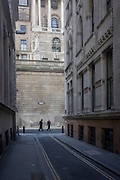 Two lunchtime pedestrians on the corner of Lothbury and Tokenhouse Yard, two narrow and historic streets with the high walls of the Bank of England in the background - in the City of London, the capital's financial district. The area was populated with coppersmiths in the Middle Ages before later becoming home to a number of merchants and bankers. Lothbury borders the Bank of England on the building's northern side. Tokenhouse St dates from Charles I and was where farthing tokens were coined. The City of London is the capital's historic centre first occupied by the Romans then expanded during following centuries until today, it has a resident population of under 10,000 but a daily working population of 311,000.