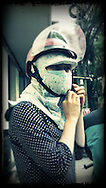 Woman dons a head cover for sun protection and a helmet before driving around Hanoi, Vietnam, Southeast Asia