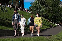 © Licensed to London News Pictures. 14/07/2021. Edinburgh, Scotland, UK. Women wearing face coverings  in Princes Street Gardens in Edinburgh as warm weather continues in Scotland. According to the Met Office, a high of 22 degrees celsius is forecast for the rest of the week. Scotland's first minister, Nicola Sturgeon has said that Scotland will move to a 'modified' form of level 0 on 19 July and 15 adults from 15 households can meet outdoors in a private garden or public place. Photo credit: Dinendra Haria/LNP