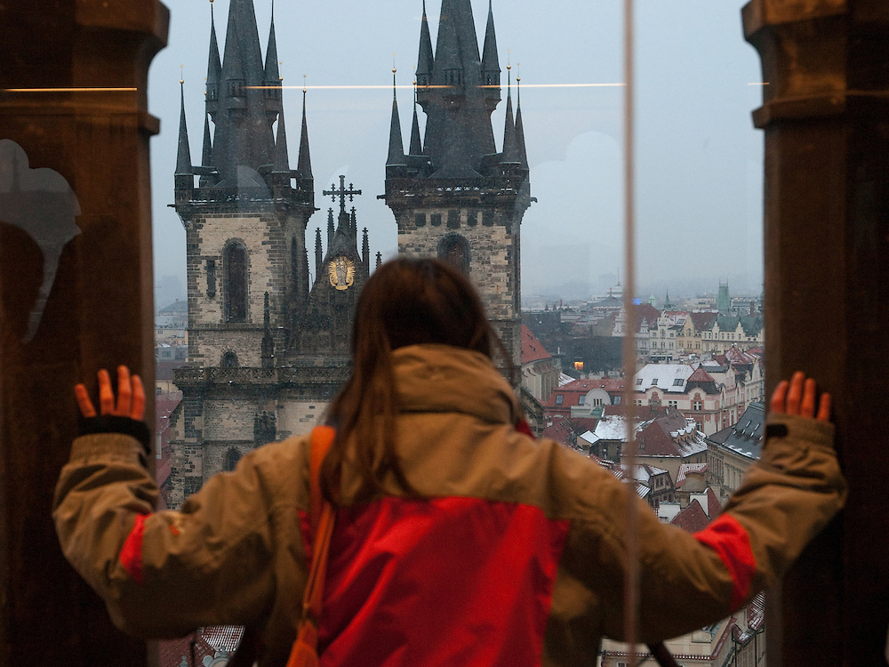 Eine junge Frau betrachtet das Prager Stadtpanorama und die Teynkirche vom Turm des Altstädter Rathaus an einem verschneiten Tag in Prag.<br /> <br /> A young woman is looking from the tower at the Old Town City Hall to the Teyn church at Old Town Square covered with snow in the city center of Prague.