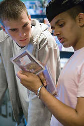 Teenaged boys looking through CDs in a music shop,