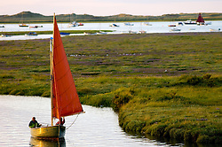 Small yacht sailing into Morston Quay, North Norfolk Coast, England, United Kingdom.