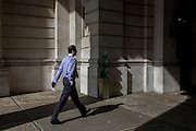 Businessman walks through sunlight at Cornhill in the City of London.