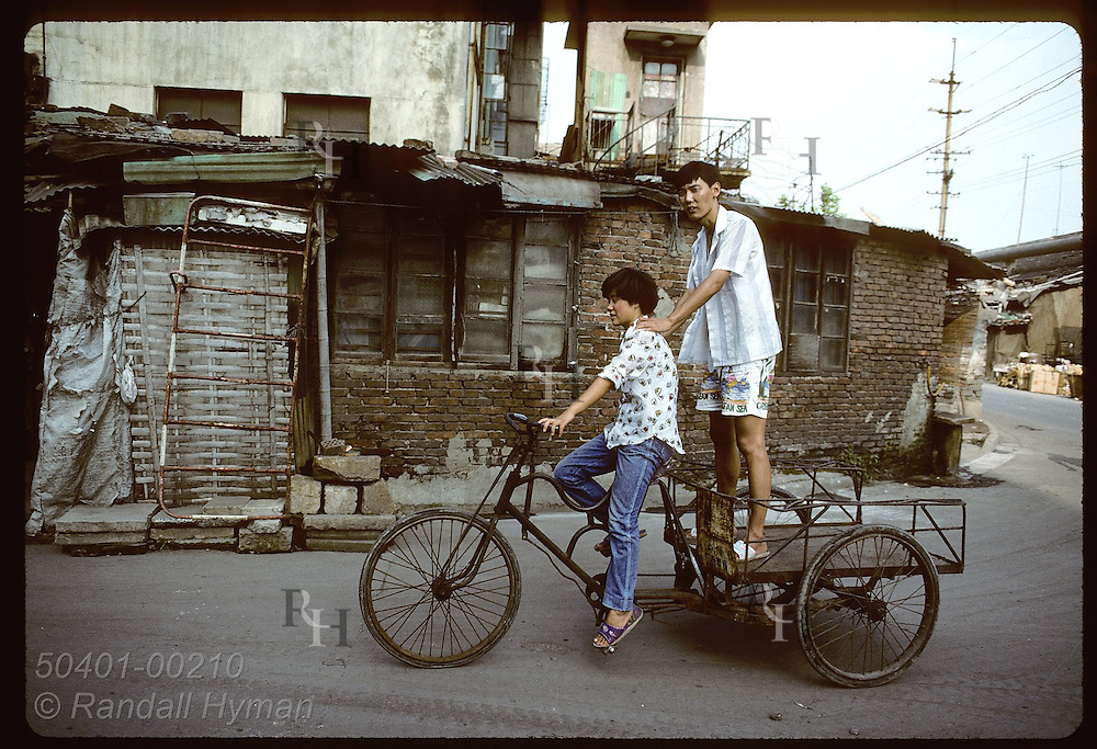 Man on back of tricycle van leans on woman pedalling through a poor industrial area of Shanghai China