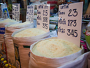 """13 FEBRUARY 2014 - BANGKOK, THAILAND: Rice for sale in Khlong Toei Market in Bangkok. The Thai government instituted a """"rice pledging scheme"""" after the election in 2011. The government agreed to buy farmers' rice crops at above market prices then planned to warehouse the rice and sell it on international markets when prices recovered. At the same time, India and Vietnam started to export large quantities of rice and the Thai government fell short of funds to pay for rice it had already purchased from farmers. Many farmers have not been paid for rice grown in 2013 and some of the rice in the Thai warehouses is allegedly rotting. Thailand has fallen from number 1 rice exporter in the world to number 3 and several government to government contracts the Thais signed with rice importing countries (like China) have been cancelled. Farmers, once key supporters of the government are now joining anti-government protests in Bangkok and occupying government ministries including the Ministry of Commerce.    PHOTO BY JACK KURTZ"""