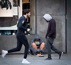 A homeless man sits bare footed on Oxford Street on a unseasonably warm Sunday morning a month before Christmas as joggers run past and don't notice him.<br />London, Great Britain <br />22nd November 2020 <br /><br /><br /><br />Photograph by Elliott Franks