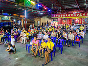 "06 DECEMBER 2015 - BANGKOK, THAILAND: People watch a Chinese opera performance at the Ruby Goddess Shrine in the Dusit district of Bangkok. Chinese opera was once very popular in Thailand, where it is called ""Ngiew."" It is usually performed in the Teochew language. Millions of Chinese emigrated to Thailand (then Siam) in the 18th and 19th centuries and brought their culture with them. Recently the popularity of ngiew has faded as people turn to performances of opera on DVD or movies. There are about 30 Chinese opera troupes left in Bangkok and its environs. They are especially busy during Chinese New Year and Chinese holidays when they travel from Chinese temple to Chinese temple performing on stages they put up in streets near the temple, sometimes sleeping on hammocks they sling under their stage.     PHOTO BY JACK KURTZ"