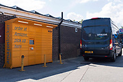 An Amazon Prime delivery van sits idle beside a yellow Amazon Locker drop box where customers can collect their online deliveries on 10th August, 2021 in Leeds, United Kingdom. Amazon is a multinational ecommerce and technology company, one of the Big FIve information technology companies in the United States.