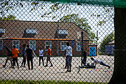 Asylum seekers playing Volleyball in the exercise yard inside Napier Barracks on the 3rd of June 2021, Folkestone, United Kingdom. Despite today's high court ruling that the Home Office's detention of Asylum seekers in Napier Barracks was unlawful, over 250 asylum seekers are still being kept in unsuitable, accommodation, they are experiencing mental health issues as well as being vulnerable to health conditions including COVID-19.  (photo by Andrew Aitchison / In pictures via Getty Images)