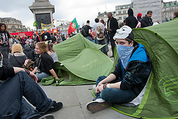 © licensed to London News Pictures. London, UK 01/05/2012. A May Day protester sits in his tent as protesters set tents to Trafalgar Square after the march, today (01/05/12).. Photo credit: Tolga Akmen/LNP