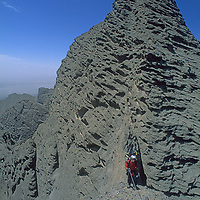 Mountaineer Mark Newcomb climbs treacherous conglomerate rock on Shipton's Arch in the arid Kara Tagh Mountains next to the hazy Taklimakan Desert near Kashagar (Kashi) in Xinjiang Province, China. Later the expedition crossed the range by descending the dangerous and unexplored slot canyon below him.