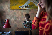 Yaroslav, 10, is checking his UNICEF video camera while inside the provisional home where he resides with his mother Olga, 36, as internally displaced persons. (IDPs) Yeroslav is taking part to the UNICEF-sponsored One Minute Junior project for internally displaced persons (IDPs), carried out by the local NGO 'Ukrainian Frontiers' in the city of Kharkiv, the country's second-largest, in the east. The conflict between Ukrainian army and Russia-backed separatists nearby, in the Donbass region, have left more than 10000 dead since April 2014, including over 1000 since the shaky Minsk II ceasefire came into effect in February 2015. The approximate number of people displaced by the conflict is 1.4 million as of August 2015. Yeroslav's mother, Olga, is also a participant to a different project of 'Ukrainian Frontiers', called 'Self-Employment', first as a beneficiary, and now as a paid hotline coordinator for people seeking jobs and formation courses.