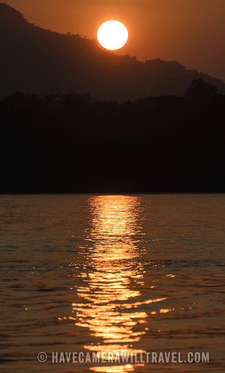The setting sun is reflected on the water just before it disappears behind a mountain nexxt to the Mekong River near Luang Prabang, Laos.