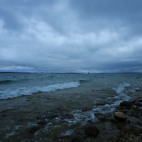"""""""Rocky Shores at McGulpin Point""""<br /> <br /> Beautiful dark and moody storm clouds envelope the straits of Mackinac with a view of Mackinac Bridge in the distance!!<br /> <br /> Mackinac Bridge by Rachel Cohen"""