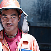 portrait of shipyard worker in Dubai with a ship in the background