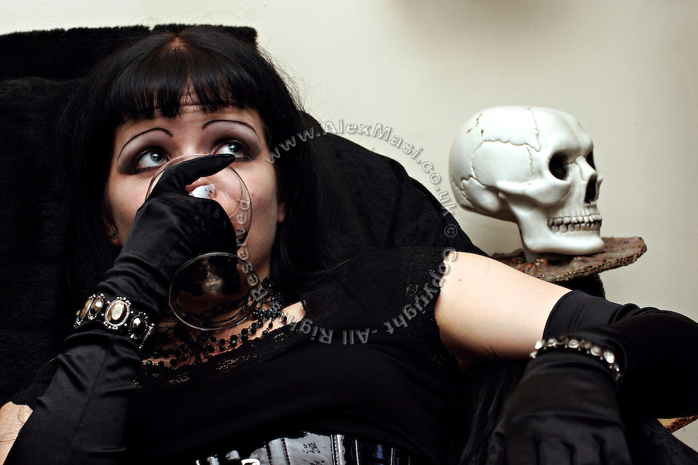 Emma Smith, 21, portrayed while savouring a glass of wine in Cecileís living room on Sunday, 15 October, 2006, in Camden Town, London, England. The Vampyre Connexion is the largest and most active of all the vampire groups in the United Kingdom, counting more than 100 members that for years have gathered regularly in London to share their common love for vampires and the Dark side of life. The Connexion raised from the hashes of the Vampyre Society, the first vampire appreciation group in 1995. The group believe in the fantasy of vampires and such creatures and live it to the full. Its  roots are to be found in the legends of Bram Stokerís Dracula. The group prints its own magazine, ëDark Nightsí featuring drawings, poetry, stories, photography and events. All of the members dress very peculiar clothing, and this is a very important part of the life of the group; it is respected with pride, taste and accuracy for the detail. Most like to dress to be elegant in a range of styles from regency to Victorian, some sew their own. In addition members visit art galleries, cemeteries, churches and cathedrals, attend gigs and concerts, and hold their own parties throughout the year, Halloween being the biggest and scariest one. Membership is open to all, the only qualification: being a love of all things Vampyric.  **ItalyOut**