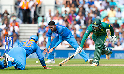Virat Kohli (capt.) of India (L) misses A run out opportunity on Quinton de Kock (wk) of South Africa (r)