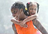 WATERBURY, CT- 30 JULY 06- 073006JT09-.Irazjah Richardson, 12, carries her screaming cousin Kourtne Johnson, 5, through the sprinkler at Chase Park in Waterbury on Sunday..Josalee Thrift Republican-American