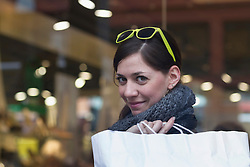Portrait of a young woman with shopping bag in the shop, Freiburg im Breisgau, Baden-Wuerttemberg, Germany