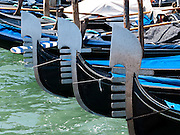 """The decorative fèrro (meaning iron) ornament on the front of gondolas can be made of brass, stainless steel, or aluminum, as counterweight for the gondolier standing near the stern. The six horizontal lines and curved top of the ferro represent Venice's six sestieri (districts) and the Doge's cap. Painting gondolas black originated as a sumptuary law reducing ostentatious competition between nobles. Gondolas are traditional, flat-bottomed Venetian rowing boats which ferry people through the canals. From a peak of ten thousand gondolas in the 1600s and 1700s, just 500 gondolas now ply the Venetian Lagoon. The oar or rèmo is held in an oar lock, or fórcola, shaped for several rowing positions. Until the early 1900s, many gondolas had a small cabin (felze) with windows which could be closed with louvered shutters--the original """"venetian blinds."""" The romantic """"City of Canals"""" stretches across 117 small islands in the marshy Venetian Lagoon along the Adriatic Sea in northeast Italy, Europe. Venice and the Venetian Lagoons are honored on UNESCO's World Heritage List."""