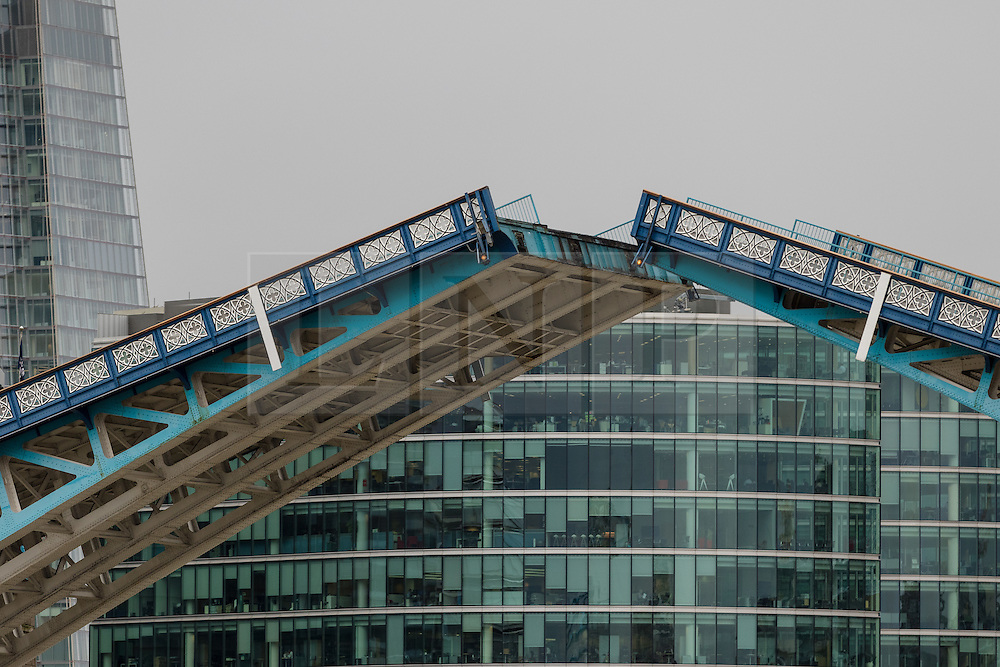 © Licensed to London News Pictures. 29/09/2016. LONDON, UK.  Tower Bridge bascules are seen raised in front of City Hall offices this morning as they lift to allow the Dutch heritage tug, MV Holland to pass underneath. 122 year old Tower Bridge will close entirely to traffic for three months from 1 October and will include major maintenance to the bridge lifting mechanisms. During this time, the bascules, which are raised 800-900 times per year will be maintained as operable to river traffic. As well as large ships, Tower Bridge regularly opens to allow vessels with tall masts to pass under, such heritage tug, MV Holland who passed underneath this morning.  Photo credit: Vickie Flores/LNP