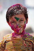 Indian boy celebrating Hindu Holi festival of colours with powder paints in Mumbai, India