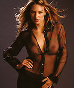 Stunning woman wearing sheer black blouse with breasts exposed and hair blowing looking at camera standing in front of a dark gray background.
