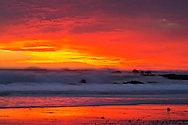 Glowing red sunset over the ocean and beach at Cayucos, San Luis Obisbo County, California